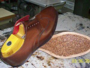 Neue Lederbrandsohle, -decksohle und Korkausballung werden eingearbeitet.